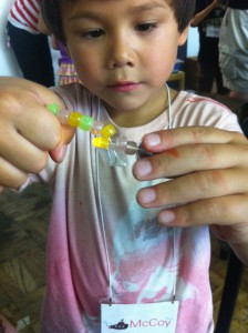 Benjiro learns about monomers and polymers through hands-on play with beads at Mini Mad Scientists Camp.