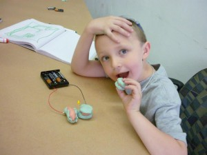 Jack plays with simple circuits, made out of conductive and insulating play dough and LED lights on electricity day of Mini Mad Scientists Camp.