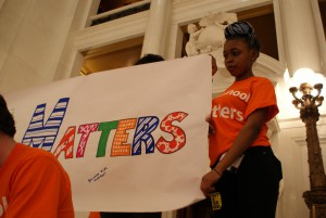 "Student from Brashear HIgh School holds up ""After School Matters"" sign"