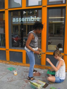"Elaysia, camper, and Julia, teacher, tag sidewalks with eco-messages in ""eco-friendly graffiti"""