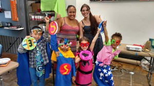 The children dressed in superhero costumes, and posing along with Angel and Fabienne.