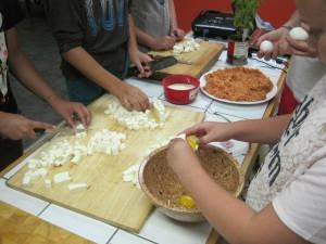 Chefs at work, making mozzarella and 'suppli al telefono'.