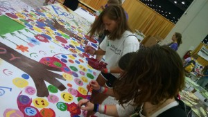Fiona, Camille, and Katie paint mural boards in the COBO Center