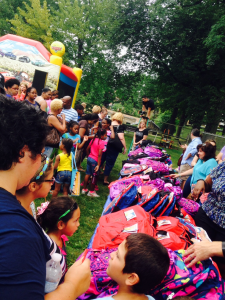Participants anxiously wait to receive their new backpacks.